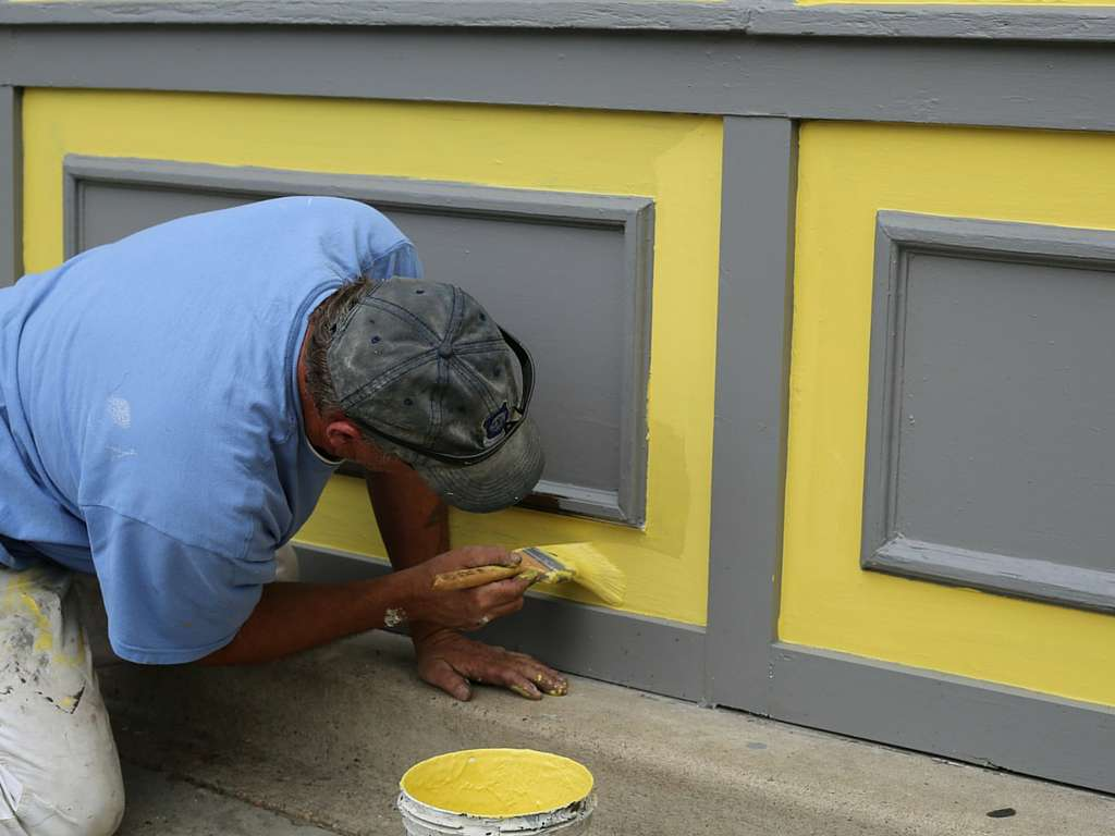pro painter is painting details of an exterior house